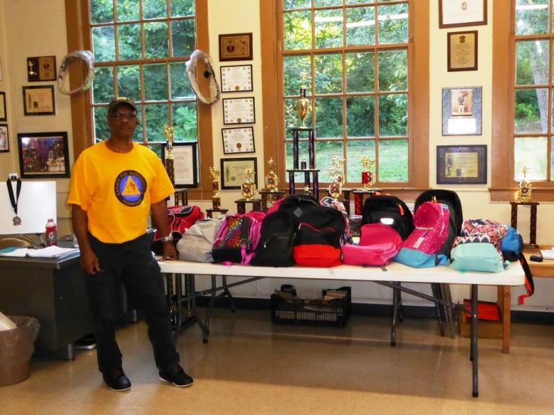 Grandmaster Willie Wilson poses with backpack display
